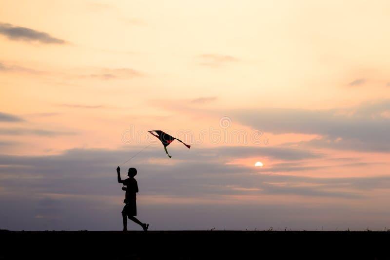 Funzionamento e volo del ragazzo della siluetta un aquilone fotografia stock libera da diritti
