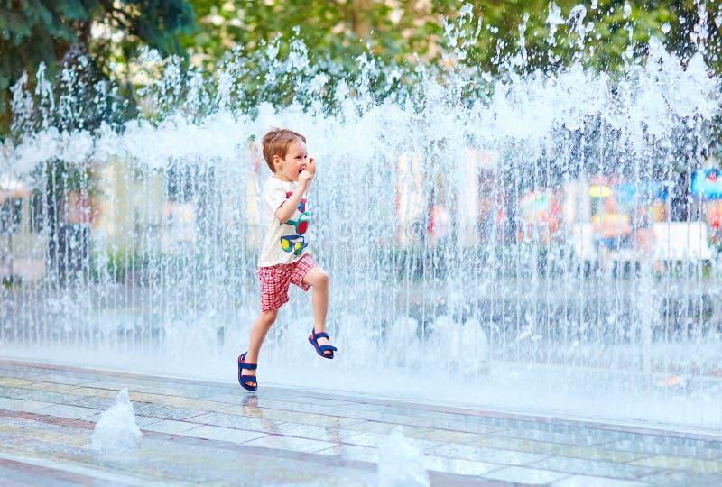 Funzionamento emozionante del ragazzo fra lo scorrimento dell'acqua nel parco della città immagini stock libere da diritti