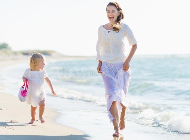 Funzionamento felice del bambino e della madre sulla riva di mare immagini stock