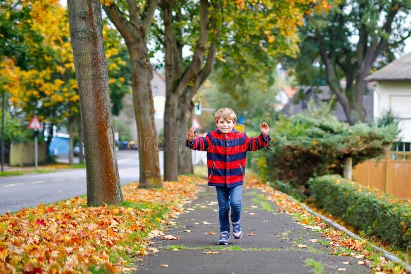 Funzionamento felice del ragazzino sulla via autunnale dopo la scuola Bambino felice circa le vacanze della scuola Bambino con mo fotografia stock