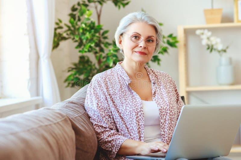 Funzionamento felice dell'anziano della donna anziana al computer portatile del computer a casa fotografie stock