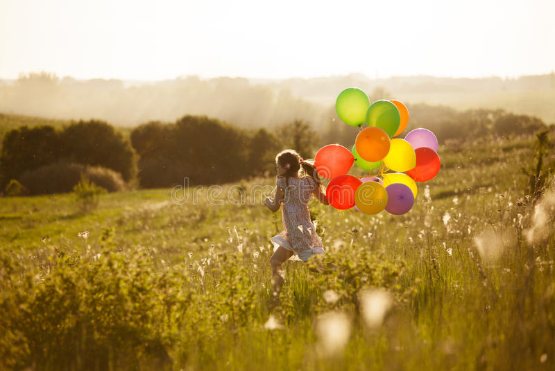 Funzionamento felice della bambina attraverso il campo fotografie stock libere da diritti
