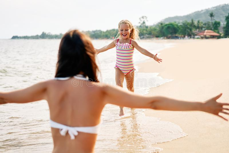 Funzionamento felice della bambina a sua madre per gli abbracci sulla spiaggia tropicale fotografia stock