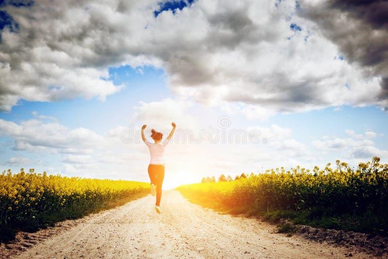 Funzionamento felice della giovane donna e saltare per la gioia fotografia stock libera da diritti