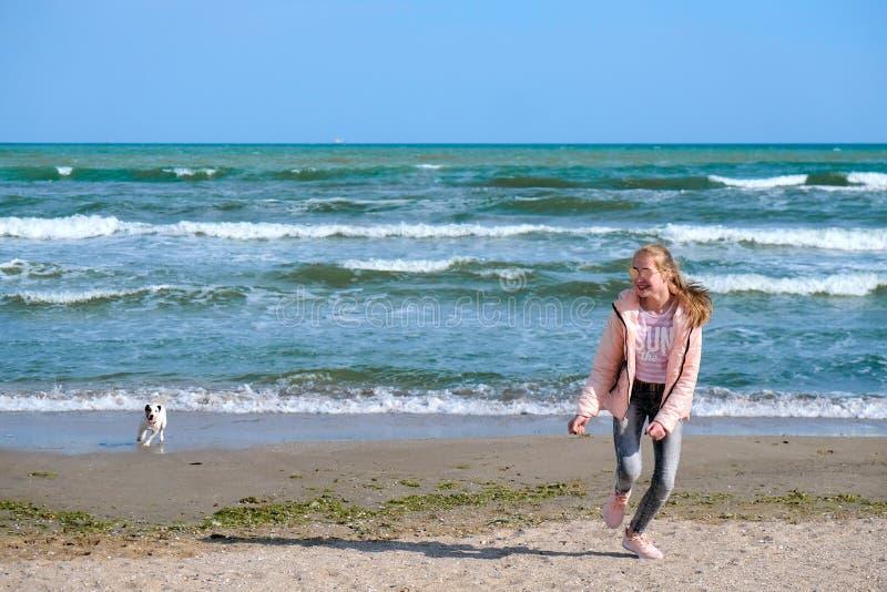 Funzionamento felice della ragazza con il cane sulla spiaggia fotografia stock