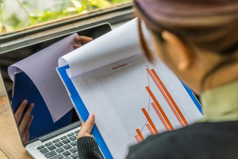 Funzionamento femminile delle free lance sul rapporto del diagramma di vendite accanto al computer portatile immagini stock