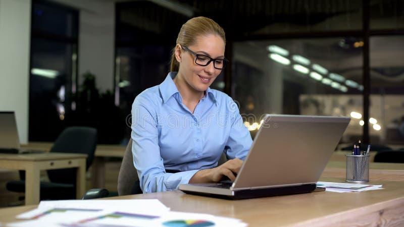 Funzionamento femminile sorridente sul progetto in ufficio, facendo uso del computer portatile vicino allo spostamento, lavoro immagine stock