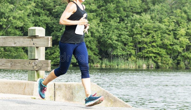 Funzionamento femminile un 10K sopra il ponte di legno con acqua dietro fotografie stock libere da diritti