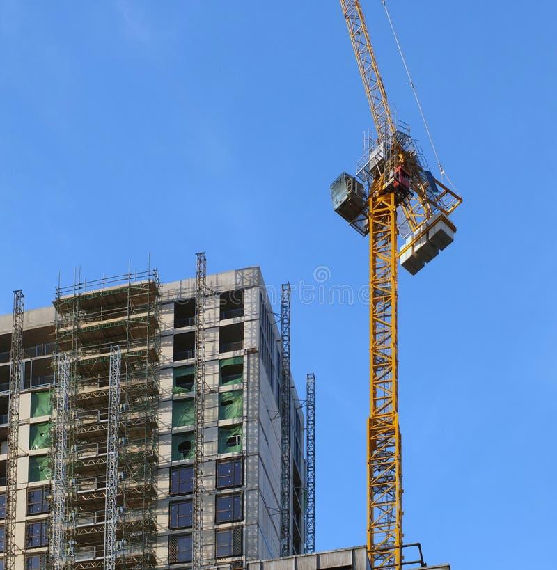 Funzionamento giallo alto della gru su una grande costruzione a più piani in costruzione immagine stock