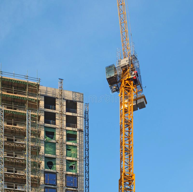 Funzionamento giallo alto della gru su una grande costruzione a pi? piani in costruzione immagine stock