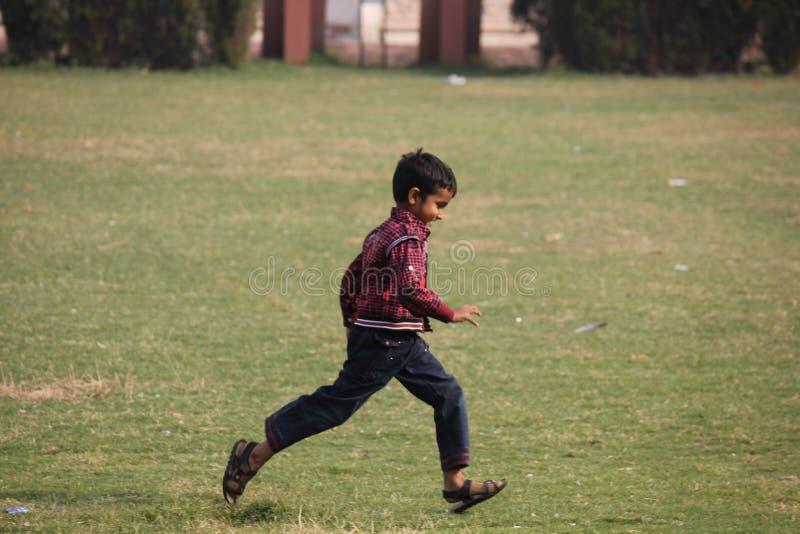 Funzionamento indiano felice del bambino nell'erba fotografie stock libere da diritti