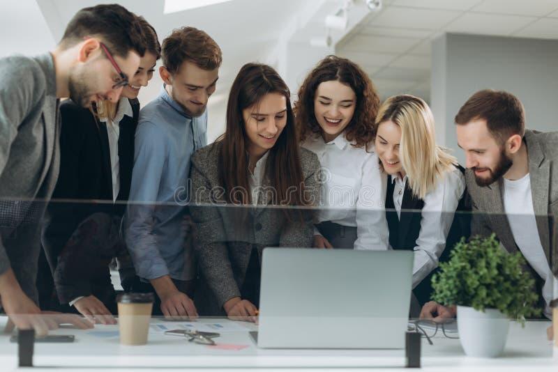 Funzionamento insieme Gruppo di giovani moderni nell'abbigliamento casual astuto che discutono affare e che sorridono nell'uffici immagine stock