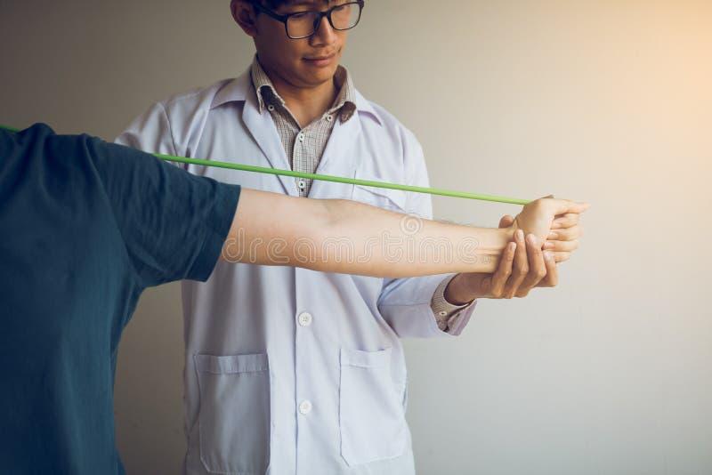 Funzionamento maschio asiatico di discesa del terapista fisico e contribuire a proteggere le mani dei pazienti con il paziente ch fotografia stock libera da diritti