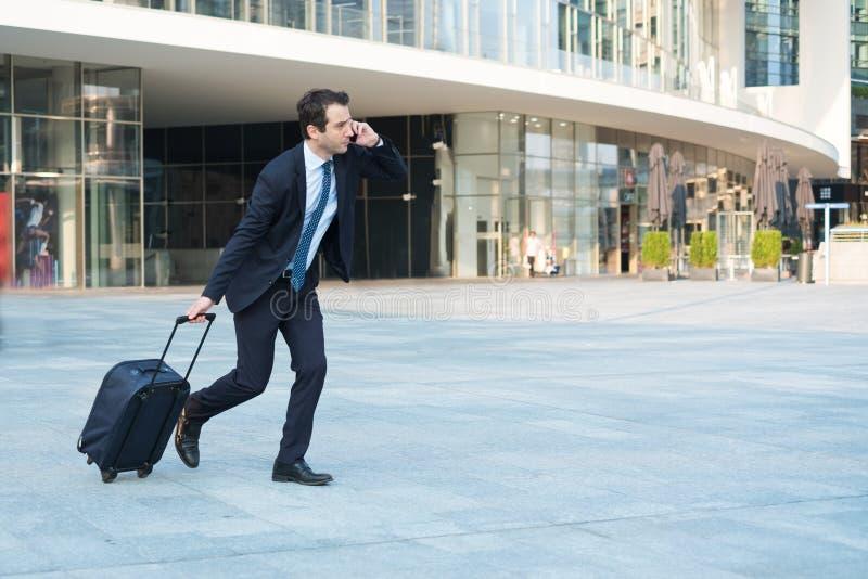 Funzionamento recente sollecitato dell'uomo d'affari con la borsa di rotolamento fotografia stock libera da diritti
