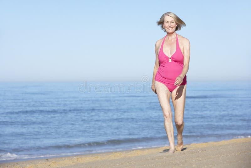 Funzionamento senior della donna lungo la spiaggia di estate immagine stock libera da diritti