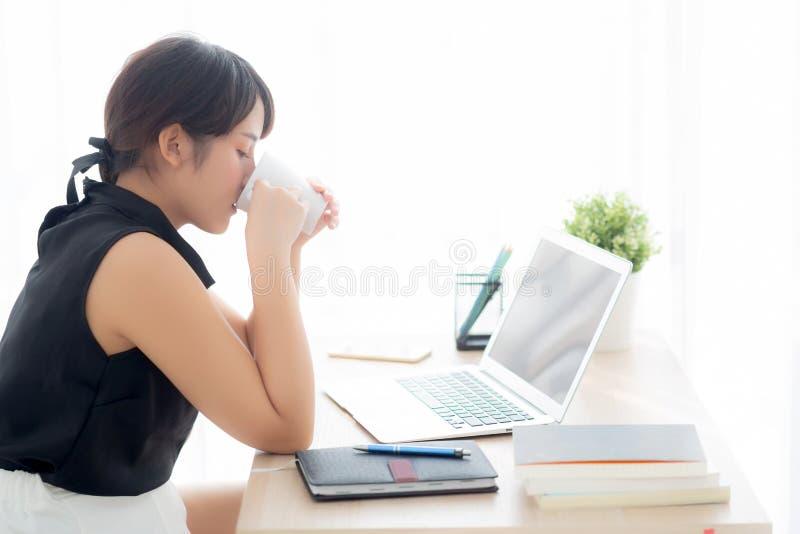 Funzionamento sorridente della bella giovane donna asiatica indipendente e sul computer portatile all'ufficio dello scrittorio co fotografie stock libere da diritti