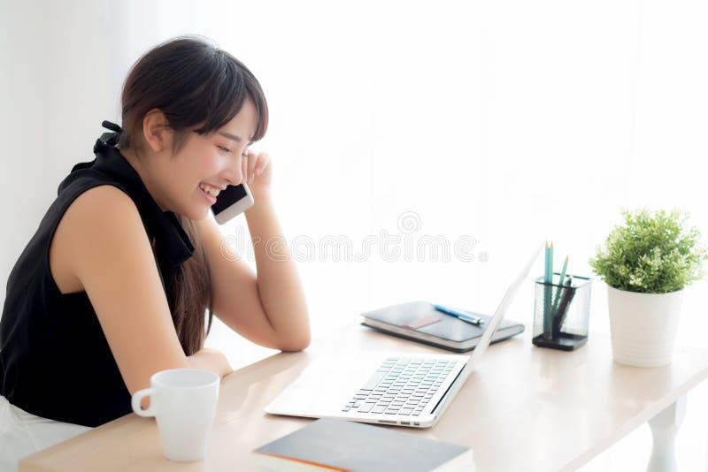 Funzionamento sorridente della bella giovane donna asiatica indipendente sul computer portatile e sullo Smart Phone mobile di con fotografia stock