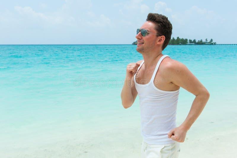 Funzionamento sorridente sulla spiaggia, isola dell'uomo delle Maldive immagini stock libere da diritti