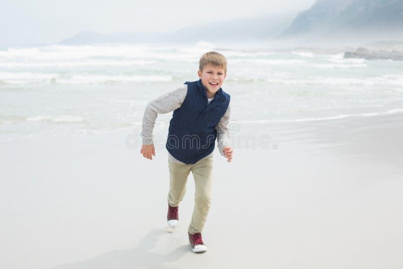 Funzionamento sorridente sveglio del ragazzo alla spiaggia fotografia stock libera da diritti