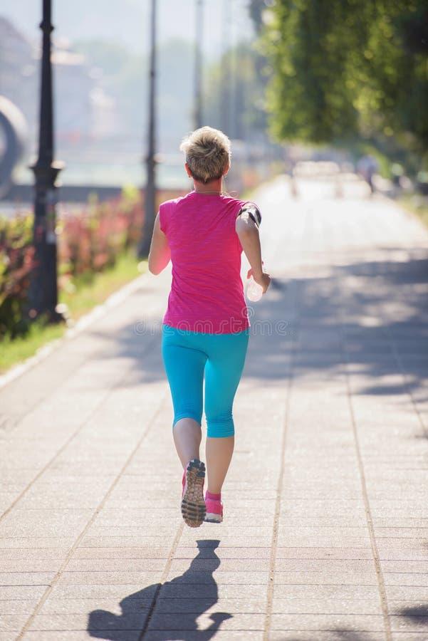 Funzionamento sportivo della donna sul marciapiede immagini stock libere da diritti