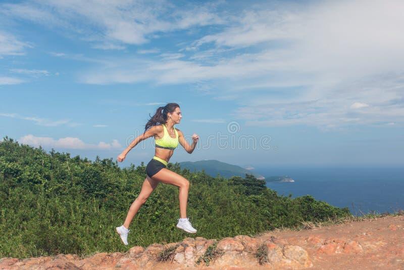 Funzionamento sportivo della traccia della ragazza sul percorso roccioso del giorno soleggiato della montagna immagine stock libera da diritti