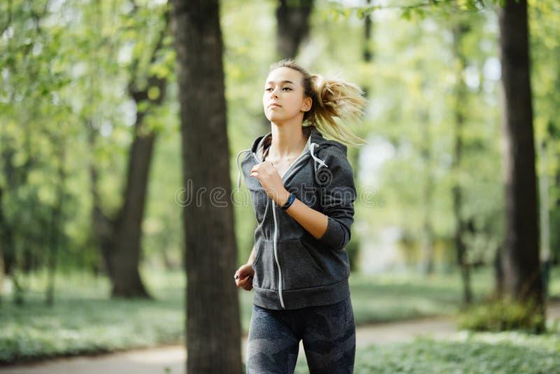 Funzionamento sportivo sorridente della donna dei giovani nel parco di mattina Ragazza di forma fisica che pareggia nel parco immagine stock libera da diritti