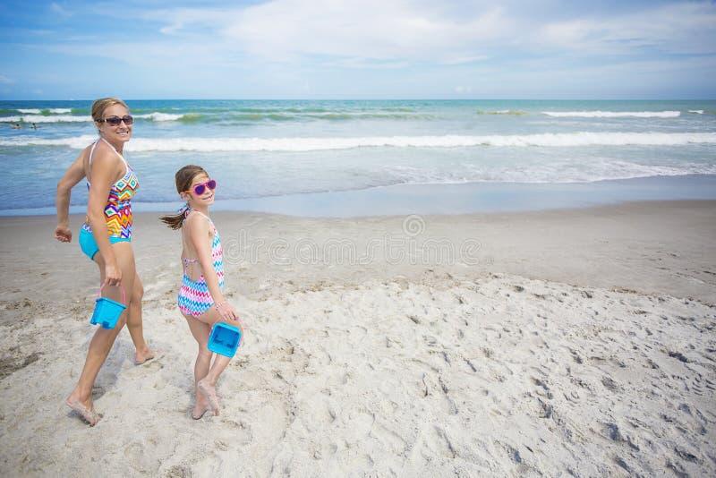 Funzionamento sveglio della famiglia e giocare alla bella spiaggia fotografia stock