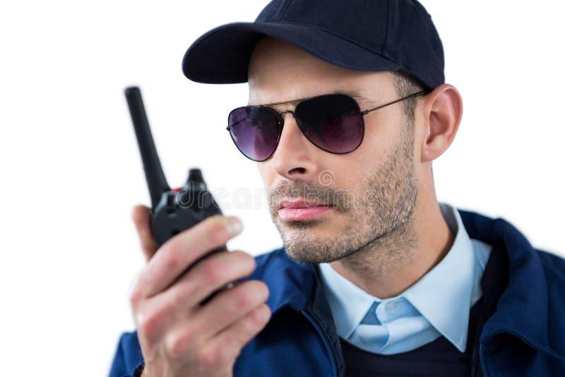 Funzionario di sicurezza bello che parla sul walkie-talkie fotografia stock libera da diritti