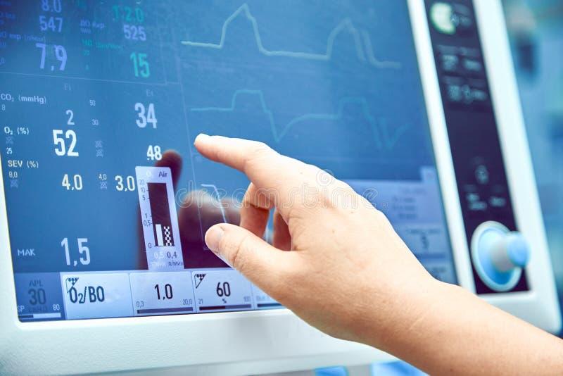 Funzione vitale paziente del ` s del monitoraggio nella sala operatoria medico che cheking alle funzioni vitali del paziente Moni fotografia stock libera da diritti