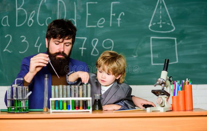 Funzioni al vostro optimum ricerca scientifica d'avanzamento del ricercatore in laboratorio padre e figlio a scuola Prova di labo fotografia stock libera da diritti
