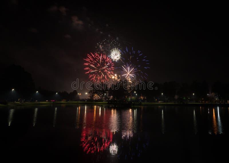 Fuochi d'artificio bianchi e blu rossi patriottici con le riflessioni in acqua immagine stock