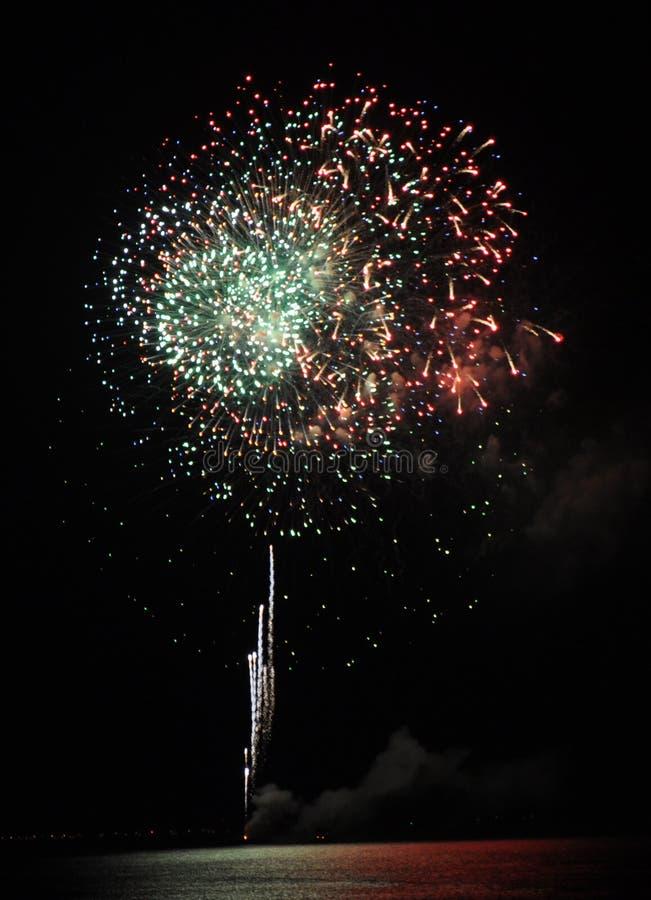 Fuochi d'artificio bianchi, verdi e rossi sopra l'oceano fotografie stock libere da diritti