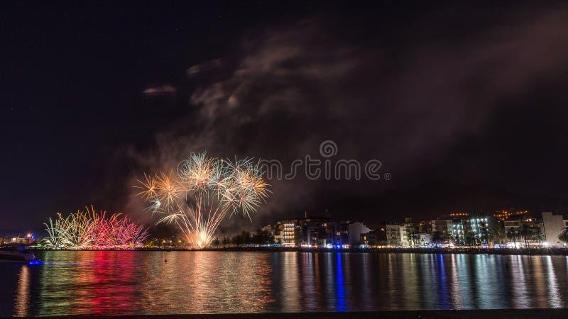 Fuochi d'artificio, castello nella spiaggia, riflessione del fuoco sul mare alla notte in rose, Catalogna, Spagna fotografia stock