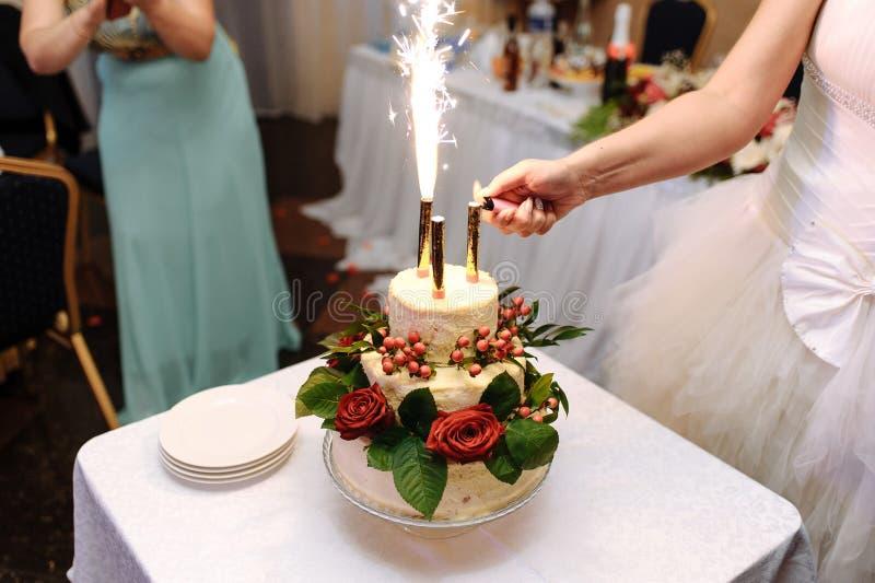 Fuochi d'artificio delle luci della sposa sulla torta nunziale su una tovaglia leggera immagine stock libera da diritti