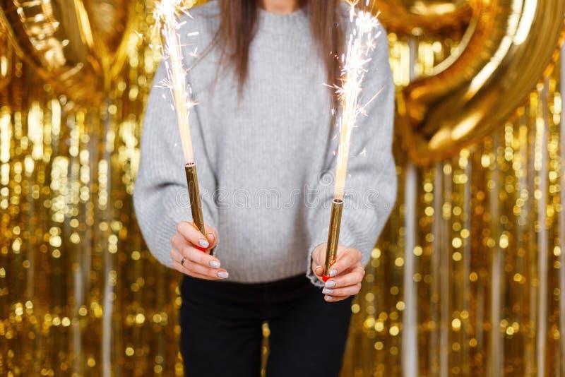 Fuochi d'artificio di stupore in mani femminili su un fondo dell'oro Primo piano Inizio del partito di divertimento fotografia stock