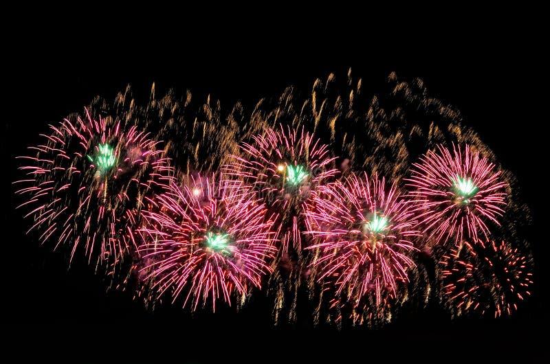 Fuochi d'artificio e scattering rosa e verdi delle scintille dell'oro fotografie stock libere da diritti