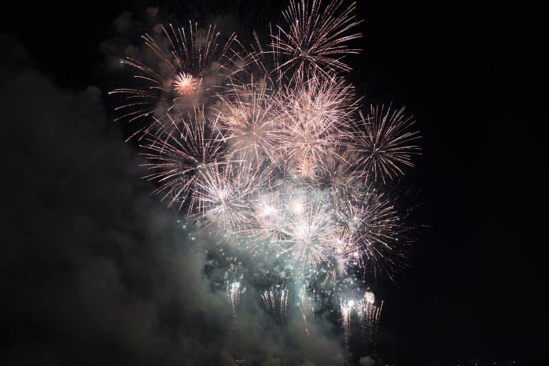 Fuochi d'artificio multipli in cielo notturno in una composizione nell'oro e nel rosso delle tonalità fotografie stock libere da diritti