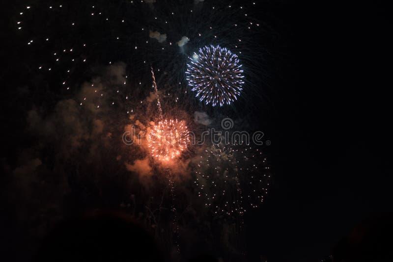 Fuochi d'artificio multipli in cielo notturno in una composizione in tonalità arancio e bianche immagine stock