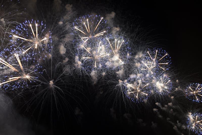 Fuochi d'artificio multipli in cielo notturno in una composizione in tonalità blu e bianche fotografie stock
