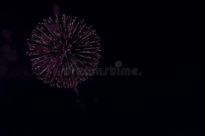 Fuochi d'artificio multipli in cielo notturno in una composizione in tonalità rosse fotografie stock