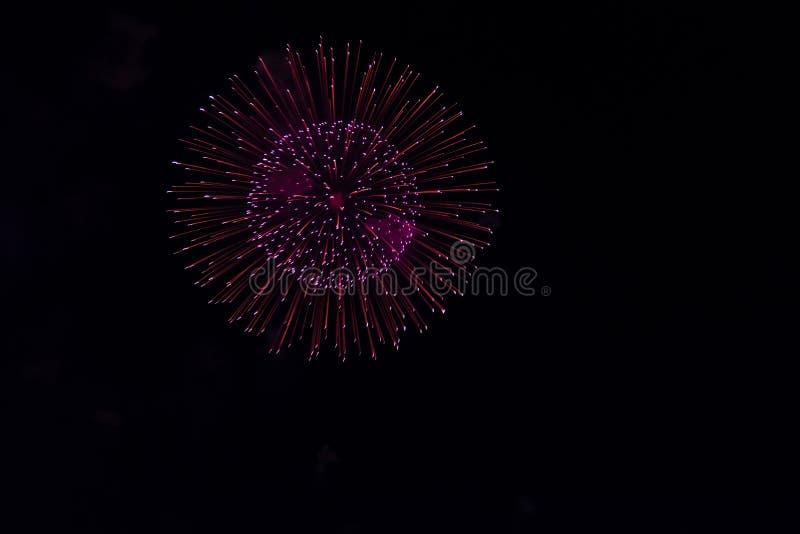 Fuochi d'artificio multipli in cielo notturno in una composizione in tonalità rosse fotografia stock