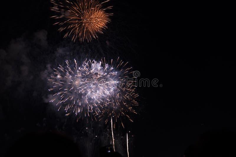 Fuochi d'artificio multipli in cielo notturno in una composizione in tonalità rosse e bianche fotografia stock libera da diritti