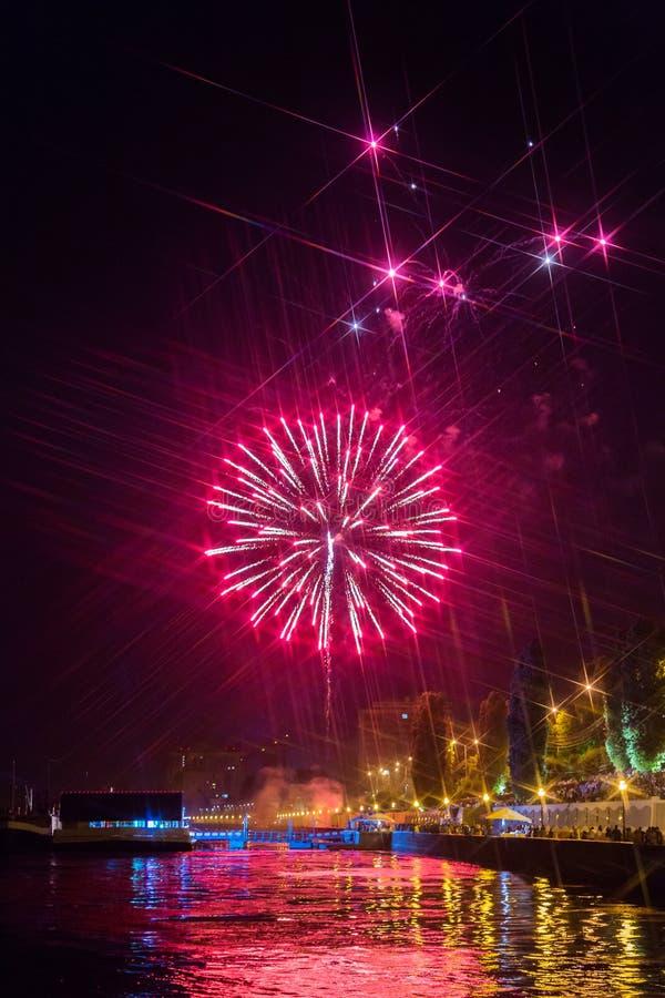 Fuochi d'artificio sopra il fiume Volga a Saratov, Russia Paesaggio urbano di sera La gente sulla via immagine stock