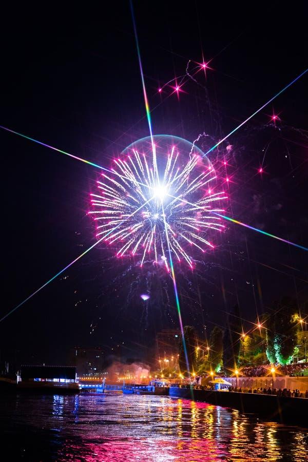 Fuochi d'artificio sopra il fiume Volga a Saratov, Russia Paesaggio urbano di sera La gente sulla via fotografia stock