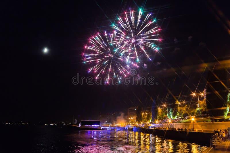Fuochi d'artificio sopra il fiume Volga a Saratov, Russia Paesaggio urbano di sera La gente sulla via La luna… in una notte nuvol immagine stock libera da diritti
