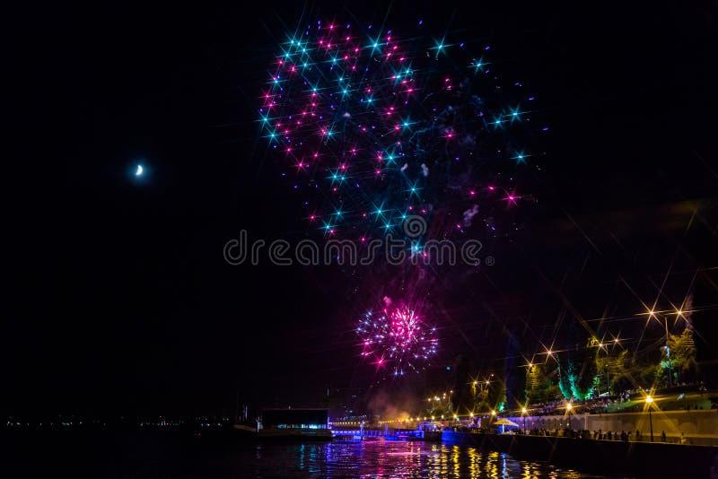 Fuochi d'artificio sopra il fiume Volga a Saratov, Russia Paesaggio urbano di sera La gente sulla via La luna… in una notte nuvol fotografia stock