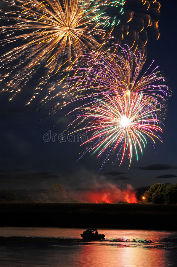 Fuochi d'artificio sopra la barca ed il fiume immagine stock