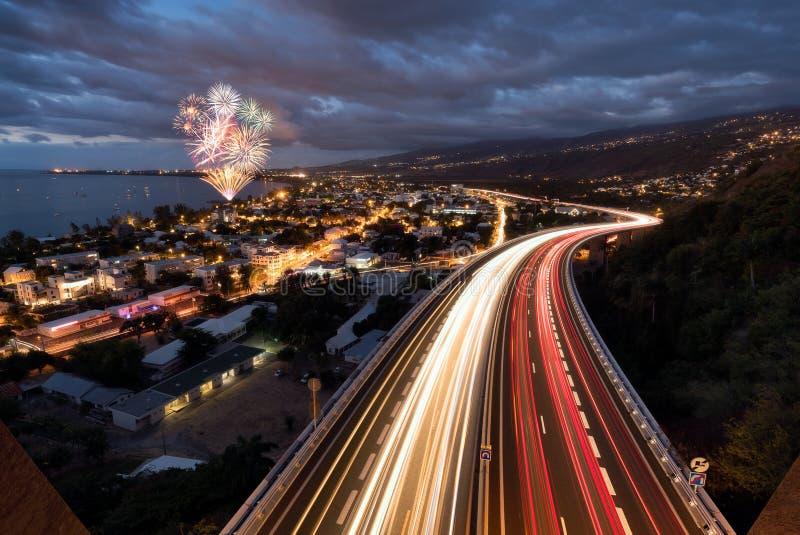 Fuochi d'artificio sopra le tracce leggere delle automobili sulla strada del tamarin in Saint Paul, Reunion Island fotografia stock libera da diritti