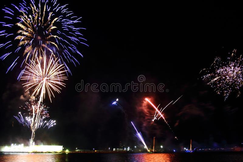Fuochi d'artificio variopinti sull'sovra-acqua nera del fondo del cielo fotografia stock libera da diritti
