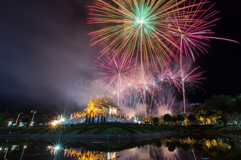 Fuoco d'artificio variopinto e tempio con la riflessione dell'acqua immagine stock libera da diritti